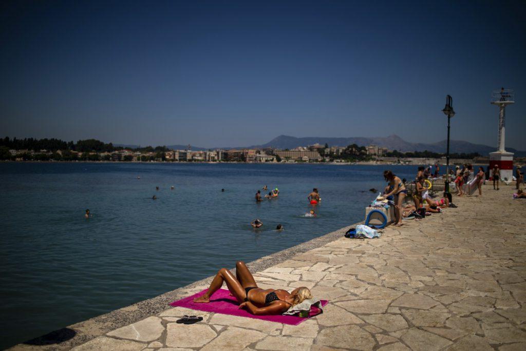 Du khách tắm nắng bên bãi biển ở Corfu vào tháng 7, khi chính phủ Hy Lạp nới lỏng các biện pháp hạn chế đi lại. Ảnh: AFP